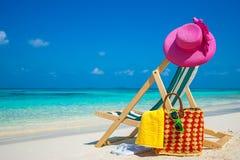 Strandstolar på den vita sanden sätter på land med molnig blå himmel och solen Royaltyfri Bild