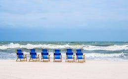 Strandstolar på den vita sandiga stranden Royaltyfri Foto