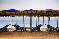 Strandstolar på sand grundar med paraplyer i sommarsäsong royaltyfria bilder
