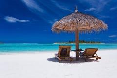 strandstolar som bedövar paraply två Arkivbild