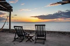 Strandstolar som förbiser solnedgång på den Holbox ön, Mexico royaltyfri bild