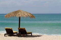 Strandstolar under ett paraply bredvid havet Arkivbild