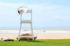 Strandstuhl auf grünem Gras, weißem Sand und Meer auf Hintergrund des blauen Himmels Lizenzfreie Stockbilder