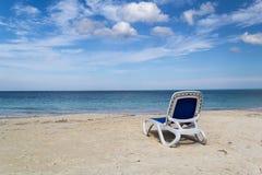 Strandstuhl auf sandigem caribean Meer Stockbilder