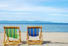Strandstuhl auf weißem Sandstrand mit haarscharfem Meer Lizenzfreie Stockbilder