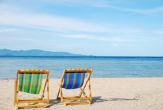 Strandstuhl auf weißem Sandstrand mit haarscharfem Meer Lizenzfreies Stockbild