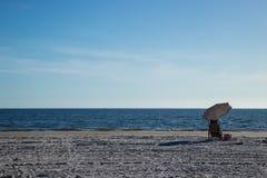 Strandstuhl, -regenschirm und -tasche der Gangeinrichtung entlang Küste stockbild