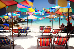 Strandstuhl und bunter Regenschirm Stockbilder