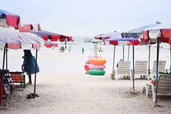 Strandstuhl und bunter Regenschirm auf dem Strand stockbild