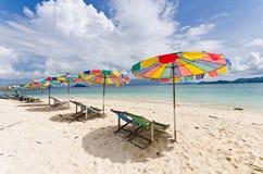 Strandstuhl und bunter Regenschirm auf dem Strand Stockfotos