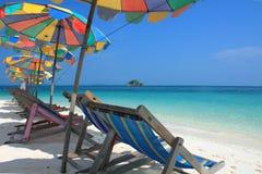 Strandstuhl und bunter Regenschirm auf dem Strand Stockfoto