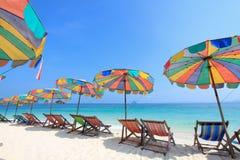 Strandstuhl und bunter Regenschirm auf dem Strand Lizenzfreies Stockbild