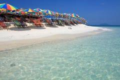 Strandstuhl und bunter Regenschirm auf dem Strand Lizenzfreie Stockfotos