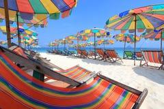 Strandstuhl und bunter Regenschirm auf dem Strand Stockfotografie