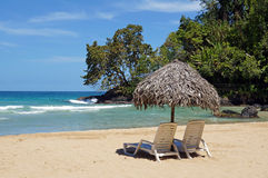 Strandstuhl und -regenschirm auf idyllischem tropischem Sand setzen auf den Strand Lizenzfreie Stockbilder