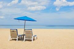 Strandstuhl und -regenschirm auf Sandstrand Lizenzfreie Stockfotografie