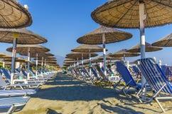 Strandstuhl und -regenschirm auf Sandstrand Lizenzfreie Stockbilder