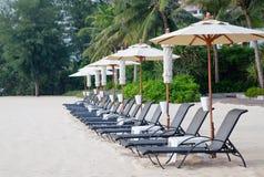 Strandstuhl und -regenschirm auf tropischem Sand setzen auf den Strand Lizenzfreie Stockfotografie