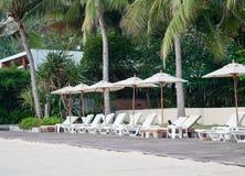 Strandstuhl und -regenschirm auf tropischem Sandstrand Stockfotografie