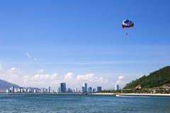 Strandtätigkeit: Parasailing, Hochgeschwindigkeitsboot zieht ein Mädchen auf einem p Stockbild