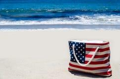 Strandtasche mit amerikanischer Flagge färbt nahe Ozean Stockfotografie