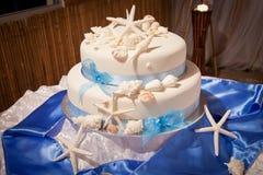 Strandtemabröllopstårta med sjöstjärnan och skal Royaltyfria Foton