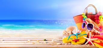 Strandtillbehör och skal på däck i Sunny Seashore royaltyfria bilder