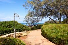 Strandtillträde förbi bana med offentliga duschar och trädgårdar royaltyfri bild
