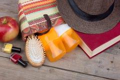 Strandtoebehoren - haarborstel, oranje handdoek, hoed, zonroom, lotion, strandzak, nagellak, boek op een bruine houten achtergron stock foto's