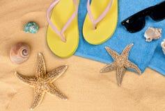 Strandtoebehoren op zand Wipschakelaars, zonnebril Royalty-vrije Stock Foto's
