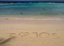 Strandurlaubsort - Sandmitteilung Stockfotos