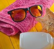 Strandurlaubsortkonzept Weibliches Strandzubehör auf einem blauen gelben hölzernen Hintergrund Shell, Gläser, Tuch, sunblock Stockfotografie
