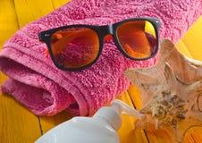 Strandurlaubsortkonzept Weibliches Strandzubehör auf einem blauen gelben hölzernen Hintergrund Shell, Gläser, Tuch, sunblock Stockbilder