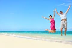 Strandvakantie - het gelukkige het paar van prettoeristen springen royalty-vrije stock afbeelding