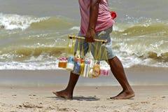 Strandverkoper bij de kust om zonnescherm te verkopen Stock Foto