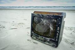 Strandverontreiniging Een geroeste en vernietigde TV op het strand die schade aan het milieu in Muisne-Eiland in Ecuador veroorza stock afbeeldingen