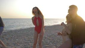 Strandvolleyball, vrolijk bedrijf die van meisjes en kerels met bal op dijk tegen overzees spelen stock videobeelden