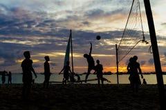 Strandvolleyboll, solnedgång, konturer av spelare på havet Arkivbilder