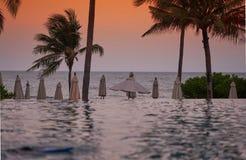 Strandvoorzijde met waterpool, kokospalm, paraplu, struik, onduidelijk beeldswi stock fotografie