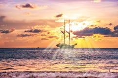 Strandzand met boot in schemering en overzeese zonsondergang en zonnestraal stock foto's