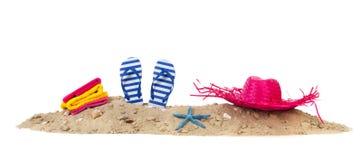 Strandzand met handdoekenwipschakelaars en hoed Stock Fotografie