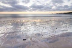 Strandzonsopgang met uit getijde Stock Foto