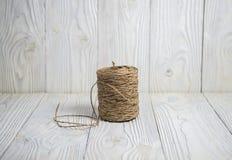Strang des Threads auf einem hölzernen Hintergrund Stockbilder