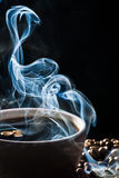 Strange blue smoke taking away from coffee. On black background Stock Photos