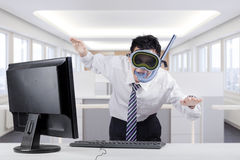 Strange businessman with goggles in office. Young businessman posing to swim while wearing goggles and snorkel with computer on desk, shot in the office Stock Photography