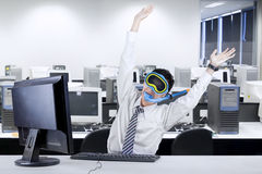 Strange businessman in office. Strange businessman wearing a snorkeling mask and celebrating his success in office Royalty Free Stock Image