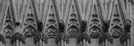 Strange characters along the main facade part 2. Shot in black and white detail on the sculpture on the facade of this historic building representing some Royalty Free Stock Photography