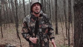 Hunter forest ranger dressed in a camouflage suit tells something to camera. Strange correspondent reporter with