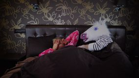 Young sleepy woman runs away. Strange couple lies in bed at stylish bedroom. Unusual man in comical unicorn mask wakes up girlfriend and scares her. Young stock video footage