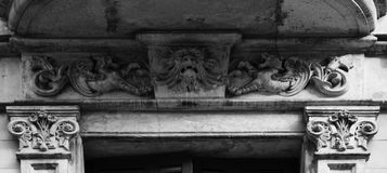 Strange creature protected by a couple of dragons. Shot in black and white, detail on the sculpture on the facade of this historic building  representing some Royalty Free Stock Images